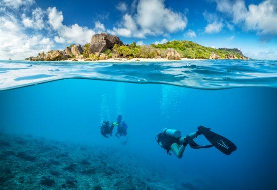 Wonderful dive destinations - Divers below the surface in Seychelles exploring corals