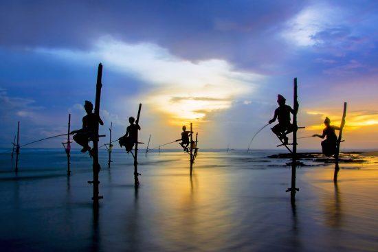 Silhouettes of the traditional Sri Lankan stilt fishermen on a s