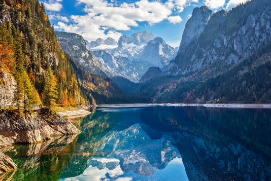 Local Dive Scene - View of idyllic colorful autumn scenery with Dachstein mountain at lake Gosau